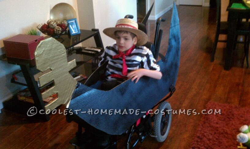I made the costume using cardboard, it is strapped to his wheelchair and open on the back so the wheelchair can still be pushed. Every year I make a