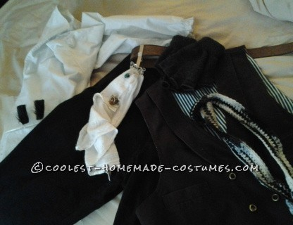 Costume pieces. White shirt, sideburns are on the sleeve, blue pin stripped pants, brown double breasted canvas vest, belt clip and ring on the rag, black and white neck scarf, brown belt.