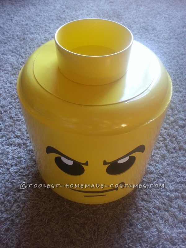 Our LEGO heads were made with cut-down buckets and PVC, then sanded to create the rounded edges.  We spray-painted them yellow, then painted on the faces.