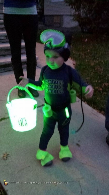 Nora out of the wagon, trick or treating with her glowing chum bucket.